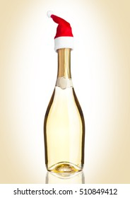 Bottle of yellow champagne with santa hat on golden background