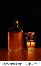 Bottle of yellow liquor with branches