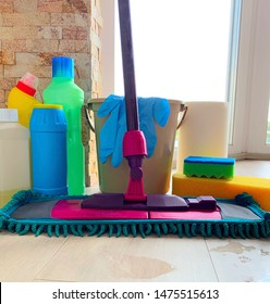 Bottled detergents, a mop and a bucket of water. A clean window, house cleaning. Rags and a blue sponge for cleaning.