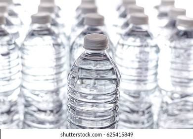 Bottled water with bright white background and one with focus. Generic with no labels.