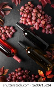 Bottled wine concept, view from above on  various types of wine bottles and ripe grapes, winery dark background - Shutterstock ID 1630915624