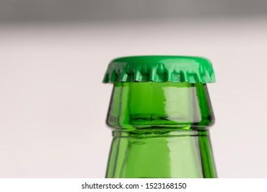Bottleneck and bottle cap of a green beer. Bottle on gradient grey background