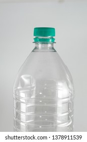 Bottleneck of a empty bottle of a liter and a half of mineral water with sea green cap and sealing ring on a white background, and space for inserts. Reuse, Eco-Friendly, Environment, Conservation