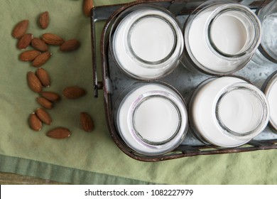 Bottles of almond milk in metal carrying case with raw almonds on green napkin, viewed from directly above.