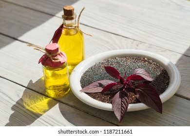 Bottles with amaranth oil, plants and amaranth seeds on a white wooden surface