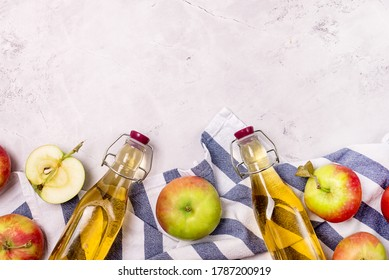 Bottles of Apple Vinegar and Ripe Apples on Kitchen Towel Light Gray Background Harvest Autumn Background Copy Space Apple Cider