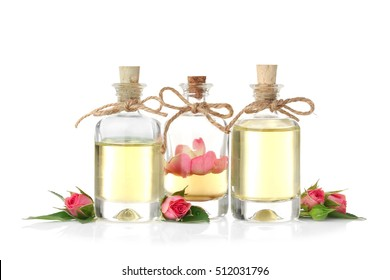 Bottles of aroma oil with roses on white background