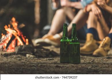 bottles of beer in hiking camp next to bonfire