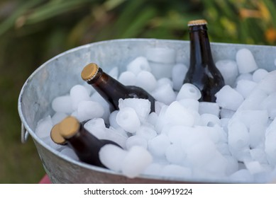 bottles of beer sitting in galvanized tub full of ice outdoors at summer party