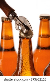 Bottles with beer and vintage opener over white background