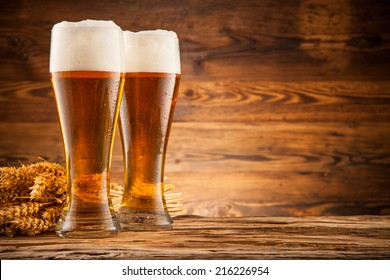 Bottles of beer with wheat ears on wooden planks