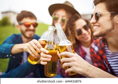 Bottles of beer.Group of friends enjoying party.people are drinking beer and laughing .  The guy plays the guitar. Everyone has a great mood. Summer time.