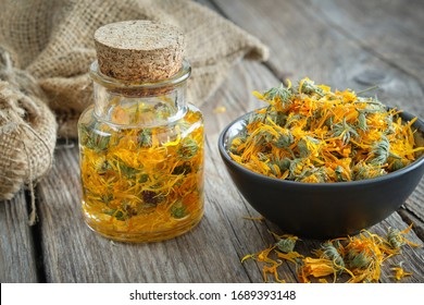 Bottles of calendula infusion or oil, healthy marigold flowers in bowl and canvas sack on background. Herbal medicine.