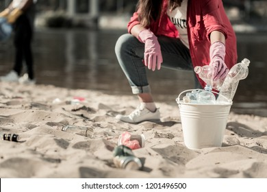 Bottles and cans. Close up of dark-haired woman wearing bright pink gloves gathering empty bottles and cans on the beach