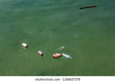 Bottles and cans in ocean. Trash on sea water surface. Ecological problem. Non-degradable seaside pollution. Human activity impact to wild life and natural environment. Oceanic pollution by tourism