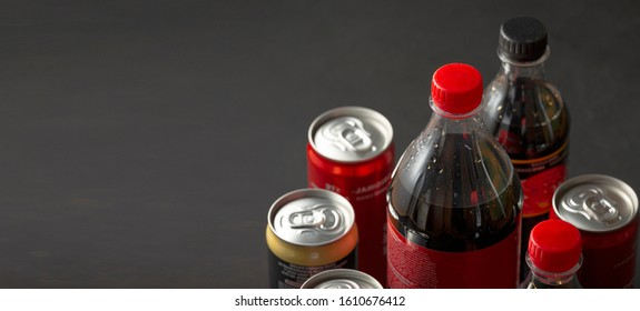 Bottles and cans on a dark background. Copy space.