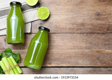 Bottles with celery juice and fresh ingredients on wooden table, flat lay. Space for text