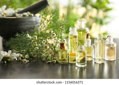 Bottles with chamomile essential oil on table