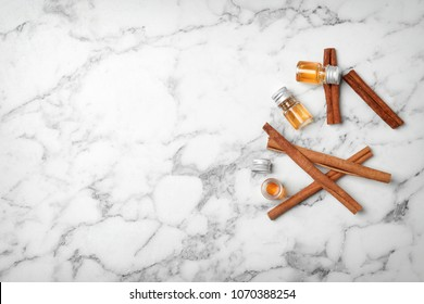 Bottles with cinnamon oil and sticks on light background