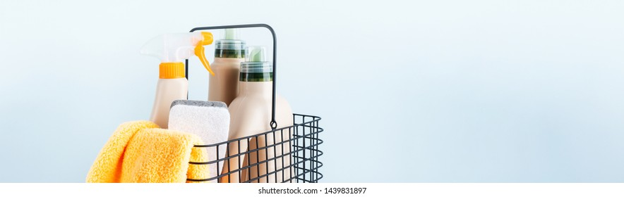 Сlose-up of bottles of cleaning products and microfiber cloth, cleaning sponge in basket on blue white background overview with space for text. Front view. Cleanliness and cleaning layout. Banner.