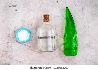 Bottles with coconut oil and aloe vera gel on gray concrete background. Body and skincare spa essentials, after sun skin treatments. Beauty blogging minimalism concept