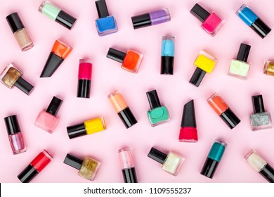 bottles of colorful nail polish on pink background. beauty and fashion trendy concept. flat lay, top view