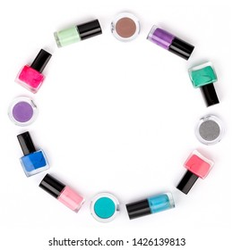 bottles of colorful nail polish on white background. beauty and fashion trendy concept. flat lay circle frame, top view