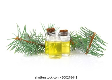 Bottles of coniferous essential oil and branch isolated on white