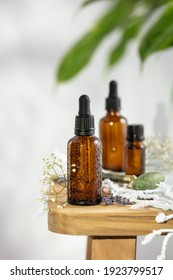 Bottles of dark amber glass with essential oil, massage jade roller and tropical leaves
