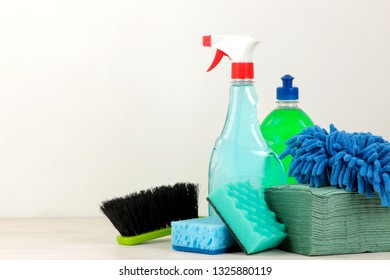 Bottles with detergent and cleaning tools in a drawer on a light background. cleaning. cleaning products. space for text