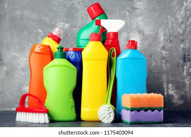 Bottles with detergent and cleaning tools on grey background