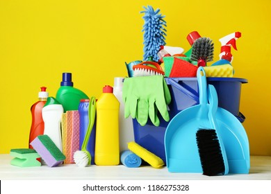 Bottles with detergent and cleaning tools on yellow background