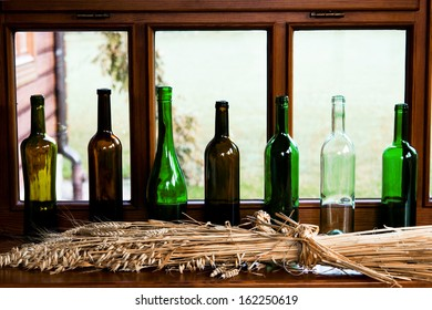 Bottles of different colors are on the windowsill