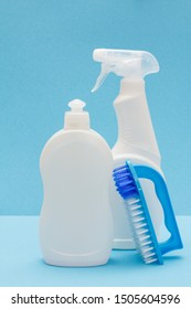 Bottles of dishwashing liquid, glass and tile cleaner, brush on blue background. Washing and cleaning concept.
