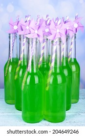 Bottles of drink with straw on table on bright background