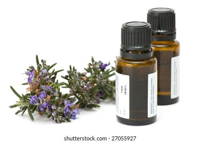 bottles of essence oil with blossoming rosemary branch, isolated on white