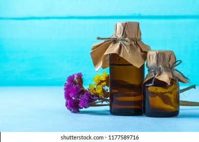 Bottles of essential and aroma oil and dried flowers on a blue background. Aroma therapy, relaxation