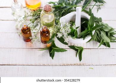 Flaschen mit ätherischem Aromaöl mit Minze auf weißem, lackiertem Holzhintergrund. Selektiver Fokus. Platz für Text.
