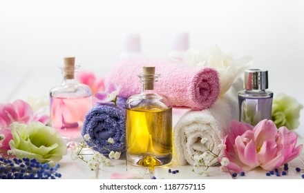 Bottles with essential aroma oil,towels different colors and fresh flowers  on white wooden background. Spa concept. Healthy cosmetic care. Place for text