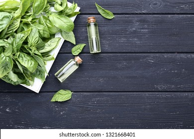 Bottles of essential oil with basil leafs on grey wooden table