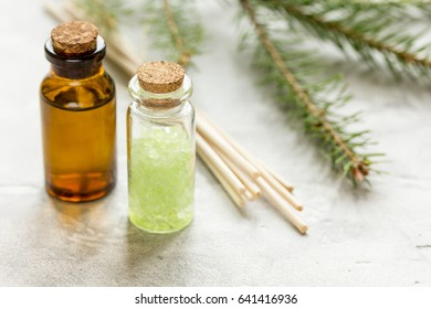 Bottles of essential oil and fir branches for aromatherapy and spa on white table background