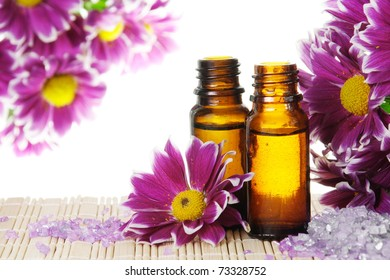 Bottles of Essential Oil with Flowers and Salt
