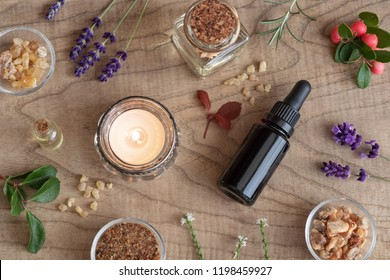 Bottles of essential oil with frankincense, wintergreen, lavender and other herbs on a wooden background