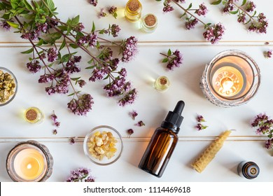 Bottles of essential oil with fresh blooming oregano twigs, frankincense resin and other herbs