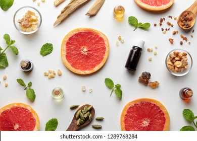 Bottles of essential oil with fresh grapefruit, peppermint, myrrh, white sandalwood and other ingredients