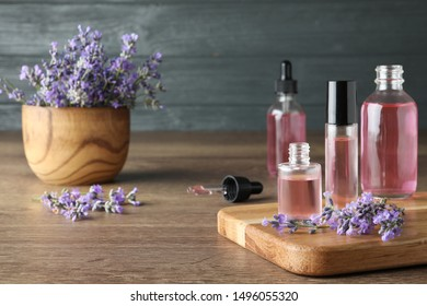 Bottles of essential oil and lavender flowers on wooden table