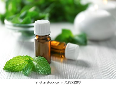 Bottles of essential oil and mint on wooden table