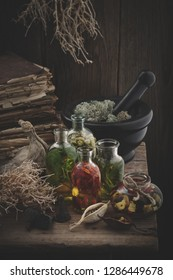 Bottles of essential oil, mortar of dried moss, old books, dry roots, nuts and plants. Herbal medicine.
