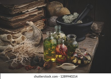 Bottles of essential oil, mortar of dried moss, old books, dry roots and plants. Herbal medicine.