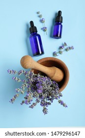Bottles of essential oil, mortar and pestle with lavender on light blue background, flat lay